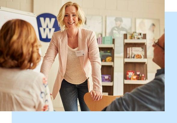 en glad blond kvinna, coach, står och pratar framför två medarbetare