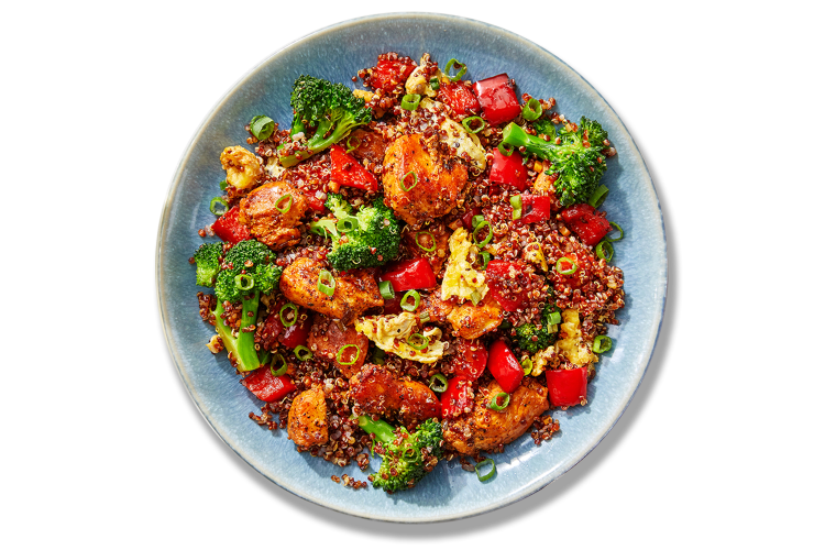 A colorful array of food sits in a round blue plate. Broccoli, scallions, and red bell peppers highlight this dish that is loaded with tasty goodness.